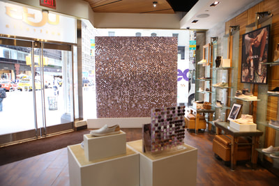 Sequin display for visual merchandising hung in window double sided.
